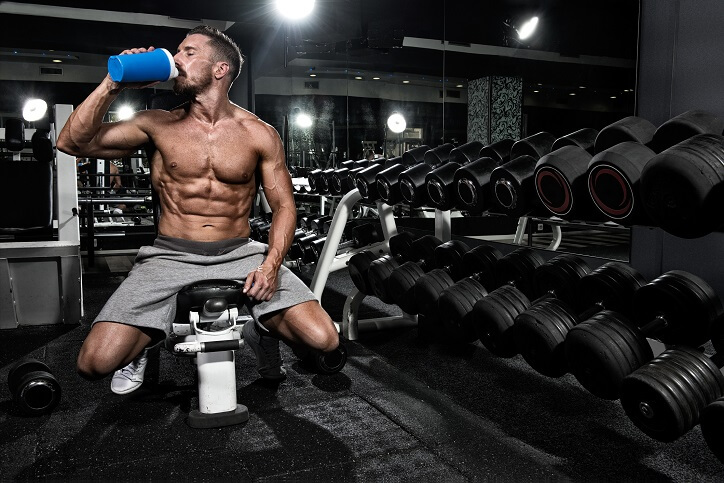 Sportowiec pijący odżywkę białkową